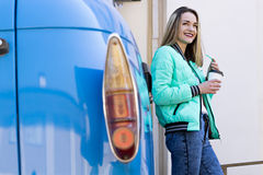 Beautiful Woman with Coffee and a Car royalty free stock image