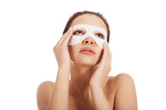 Beautiful woman with collagen mask on eyes. Royalty Free Stock Images