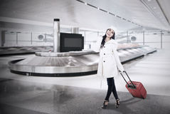 Beautiful woman collect luggage at airport. Beautiful woman with winter coat collect her luggage at airport royalty free stock photo