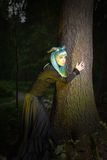 Beautiful woman with color hair and horns in the forest holds a tree Royalty Free Stock Photo