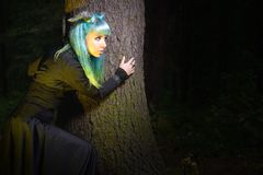 Beautiful woman with color hair and horns in the forest holds a tree Stock Photos