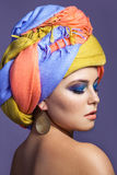 Beautiful woman with colored headwear and blue makeup. Royalty Free Stock Image