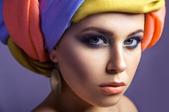 Beautiful woman with colored headwear and blue makeup. Stock Photography