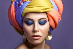 Beautiful woman with colored headwear and blue makeup. Stock Photo