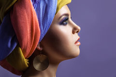 Beautiful woman with colored headwear and blue makeup. Stock Images