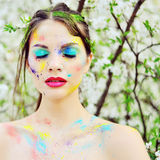 Beautiful woman with colored paint on face outdoor Royalty Free Stock Images