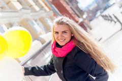 Beautiful woman with colorful balloons. Portrait of a beautiful young woman, long-haired blonde. she wears a black coat, a bright pink scarf. color sunglasses Stock Photos