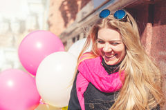Beautiful woman with colorful balloons. Portrait of a beautiful young woman, long-haired blonde. she wears a black coat, a bright pink scarf. color sunglasses royalty free stock photos