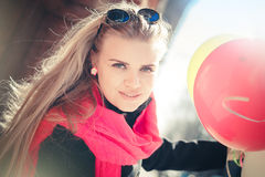 Beautiful woman with colorful balloons. Portrait of a beautiful young woman, long-haired blonde. she wears a black coat, a bright pink scarf. color sunglasses Stock Photo