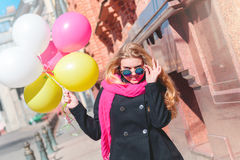 Beautiful woman with colorful balloons. Portrait of a beautiful young woman, long-haired blonde. she wears a black coat, a bright pink scarf. color sunglasses Stock Photography