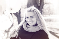 Beautiful woman with colorful balloons. Portrait of a beautiful young woman, long-haired blonde. She wears a coat and scarf. smiling woman. holding balloons Stock Photography