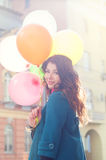 Beautiful woman with colorful balloons. Portrait of a beautiful young woman with multi-colored balloons. Woman with long curly brown hair, smile. A woman dressed Royalty Free Stock Photo
