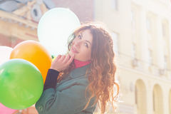 Beautiful woman with colorful balloons. Portrait of a beautiful young woman with multi-colored balloons. Woman with long curly brown hair, smile. A woman dressed Stock Photos
