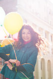 Beautiful woman with colorful balloons. Portrait of a beautiful young woman with multi-colored balloons. Woman with long curly brown hair, smile. A woman dressed Stock Photo