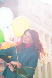 Beautiful woman with colorful balloons. Portrait of a beautiful young woman with multi-colored balloons. Woman with long curly brown hair, smile. A woman dressed Stock Image