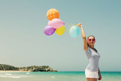 Beautiful woman with colorful balloons. On seaside Royalty Free Stock Image