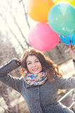 Beautiful woman with colorful balloons in the spring park. Portrait of a beautiful young woman with multi-colored balloons. Woman with long curly brown hair Stock Image