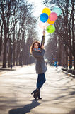 Beautiful woman with colorful balloons in the spring park. Portrait of a beautiful young woman with multi-colored balloons. Woman with long curly brown hair Royalty Free Stock Photography