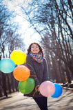 Beautiful woman with colorful balloons in the spring park. Portrait of a beautiful young woman with multi-colored balloons. Woman with long curly brown hair Stock Photo
