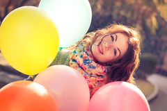 Beautiful woman with colorful balloons in the spring park. Portrait of a beautiful young woman with multi-colored balloons. Woman with long curly brown hair Stock Photos