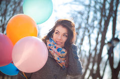 Beautiful woman with colorful balloons in the spring park. Portrait of a beautiful young woman with multi-colored balloons. Woman with long curly brown hair Royalty Free Stock Image
