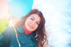 Beautiful woman with colorful balloons in the spring park. Portrait of a beautiful young woman with multi-colored balloons. Woman with long curly brown hair Stock Photography