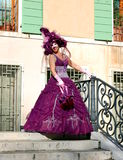 Beautiful woman in colorful costume and mask on one of Venetian bridges Stock Photos