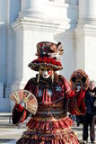 Beautiful woman in colorful costume and mask during Venetian carnival Stock Photo