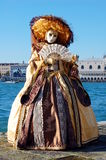 Beautiful woman in colorful costume and mask, view on Piazza San Marco Royalty Free Stock Image