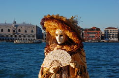 Beautiful woman in colorful costume and mask, view on Piazza San Marco Royalty Free Stock Photos