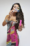 Beautiful woman in colorful dress. Woman playing with bubble solution, focus in front Stock Images