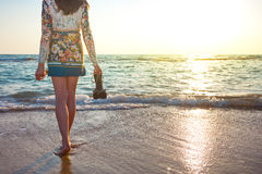 Beautiful woman in colorful dress standing on the beach near the ocean and looking far away at the sunset Royalty Free Stock Photos