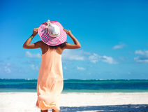 Beautiful woman in colorful sunhat and dress walking near beach Royalty Free Stock Photos