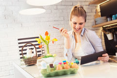 Beautiful woman coloring Easter eggs Stock Photos