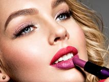 Beautiful woman colors lips with red lipstick. Makeup. stock photography
