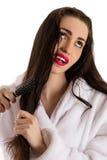 Beautiful woman combing hair with sad face Stock Photos