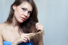 Beautiful woman combing her hair. By wooden brush Stock Photography