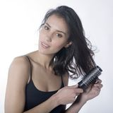 Beautiful woman combing her hair. A studio portrait of a beautiful young woman combing her  dark hair Stock Image