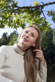 Beautiful woman combs long hair in the summer day on the river bank Royalty Free Stock Image