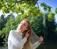 Beautiful woman combs long hair in the summer day Stock Photography