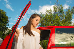 Beautiful woman comming out from her red car in a sunny day Stock Photos