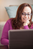 Beautiful woman with computer. Beautiful brazilian woman at home relaxing and using a laptop computer Royalty Free Stock Photo