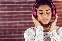 A beautiful woman concentrated on her music. On a brick wall Royalty Free Stock Image