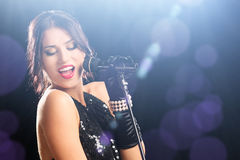 Beautiful woman during a concert holding a microphone Royalty Free Stock Images