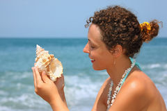Beautiful woman considering seashell on seacoast Royalty Free Stock Photography