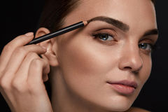 Beautiful Woman Contouring Eyebrows With Pencil. Beauty stock photos