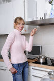 Beautiful woman cooking in a modern kitchen. Beautiful woman cooking using in a modern kitchen tasting her food stock images