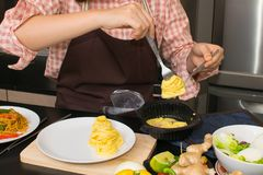 Beautiful woman cooking in new kitchen making healthy food with Stock Images