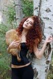 Beautiful woman in corset with fur dreams near birch Stock Image