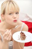 Beautiful woman on couch eating cake. Stock Photo